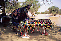 Akadaney, Central Niger, West Africa.  Fulani Nomads.  Fulani Woman Placing Straw Mats on Portable Bed.