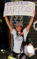 """Venezuela: Caracas,15/02/14 <br /> A young woman carry a banner that reads """"we are tired"""" during a protest march of thousands of students calling for the release of  young arrested in last Feb12 protest, where two students and a member of a  pro-government paramilitary group killed.<br /> Carlos Hernandez/Archivolatino"""