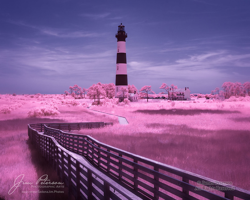 """Bodie Island Light Station (Infrared).  This lighthouse was built in 1872 to help ships navigate near North Carolina's treacherous Outer Banks, known as """"The Graveyard of The Atlantic."""" It is still in operation today with its original first-order Fresnel lens, though it no longer uses an oil lamp (it was electrified in 1932).  It is situated just south of Nags Head in the Cape Hatteras National Seashore, and all of its property is now part of the National Park Service except the tower itself, which still belongs to the US Coast Guard.<br /> <br /> This image was processed to emulate the look of Kodak's long-discontinued Aerochrome color infrared film.<br /> <br /> Image ©2021 James D. Peterson<br /> <br /> Tech info: Nikon D3200 camera (modified for infrared with 590nm filter) with Nikon 10-24mm lens at 24mm, 1/160 sec. at f16, ISO 200"""