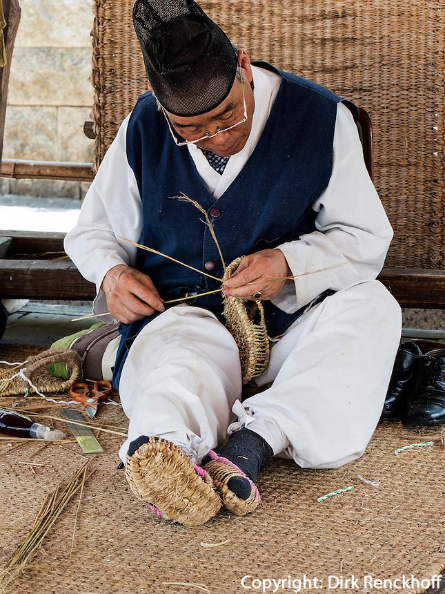 traditioneller Strohflechter mit Kopfbedeckung Tanggon  im Namsangol Hanok Village, Seoul, Südkorea, Asien<br /> traditional straw plaiting in Namsangol Hanok village, Seoul, South Korea, Asia
