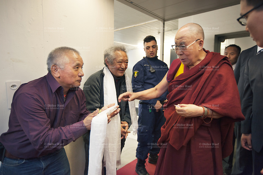 """Switzerland. Basel. St. Jakobshalle. Rinzin Lang (L) and Thubten Purang (C) greet and pay tribute to His Holiness the Dalai Lama. They offer him scarfs, called khata, with a humble bow before them. In most cases the giver will receive his or her Khata back from the given, as a token of blessing back to them. When a Khata is offered to His Holiness the Dalai Lama and received back, it will be cherished and preciously kept as it is now a very special blessing, a talisman and protector. The two men are part of Aeschimann's children who arrived 50 years ago in Switzerland to receive custody on a private initiative by an influential Swiss industrialist, Charles Aeschimann. In 1962, Charles Aeschimann agreed with the Dalai Lama to take 200 children and place them in Swiss foster homes and give them a chance for a better life and a good education. Most of the children still had parents in exile or in Tibet, just a few were orphans. The 14th and current Dalai Lama is Tenzin Gyatso, recognized since 1950. He is the current Dalai Lama, as well as the longest-lived incumbent, well known for his lifelong advocacy for Tibetans inside and outside Tibet. Dalai Lamas are amongst the head monks of the Gelug school, the newest of the schools of Tibetan Buddhism. The Dalai Lama, also called """" Ocean of Wisdom"""" is considered as the incarnation of Chenresi, the Bodhisattva of compassion who is also the protective deity of Tibet. 8.02.2015 © 2015 Didier Ruef"""