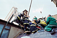 Firefighters and paramedic ambulance crews attending the rescue of a workman working on the roof of a building who was crushed when a crane dropped a pallet of bricks onto him. He was trapped under the bricks and was knocked unconscious. He had to be lifted over the building on a stretcher attached to the cage of a hydraulic platform fire engine. It was vital that he was not tilted in any way which made the rescue very difficult to execute...© SHOUT. THIS PICTURE MUST ONLY BE USED TO ILLUSTRATE THE EMERGENCY SERVICES IN A POSITIVE MANNER. CONTACT JOHN CALLAN. Exact date unknown.john@shoutpictures.com.www.shoutpictures.com.