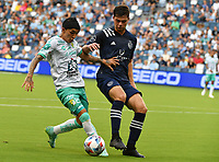 KANSAS CITY, KS - AUGUST 10: Omar Fernandez #25 of Club Leon FC shields the ball away from Kaveh Rad #48 of Sporting Kansas City during a game between Club Leon FC and Sporting KC at Children's Mercy Park on August 10, 2021 in Kansas City, Kansas.