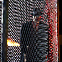 Black man in coat standing behind chain link fence<br />