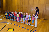 MR / Schenectady, NY. Zoller Elementary School (urban public school). Kindergarten inclusion classroom. Students line up in front of their teacher in school gym after completing physical education class. After physical activity, they need to settle down. She is focusing their attention by having them follow directions and imitate her motions. MR: War15. ID: AM-gKw. © Ellen B. Senisi.