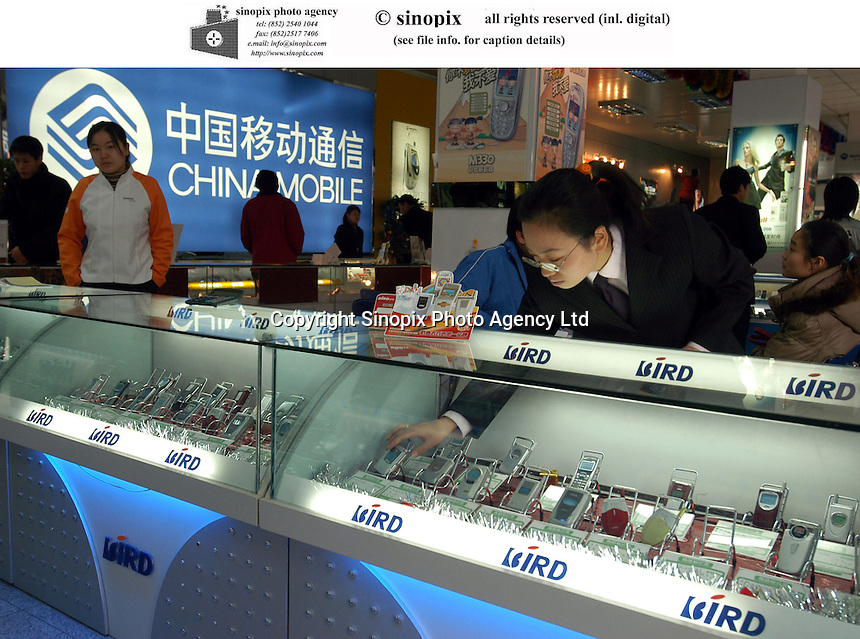 A shop employee tidies up Ningbo Bird cell phones at a telecom store in Wangfujing, Beijing, China..