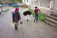 Diqing Tibetan Autonomous Prefecture, Yunnan Province, China - Members of a Tibetan family walk in the rain, August 2018.