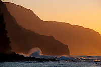 The setting sun casting a warm glow over the cliffs of Na Pali near Ke'e Beach, Kauai.