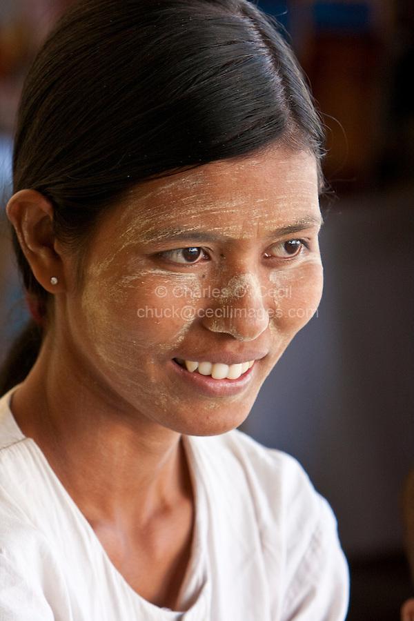 Myanmar, Burma.   Burmese Woman Wearing Thanaka Paste as a Cosmetic Sunscreen.  Shwezigon (Shwezegon)  Pagoda, Nyaung Oo, near Bagan.