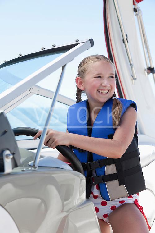 USA, Florida, St. Petersburg, Smilling girl (10-11) wearing life jacket steering speedboat