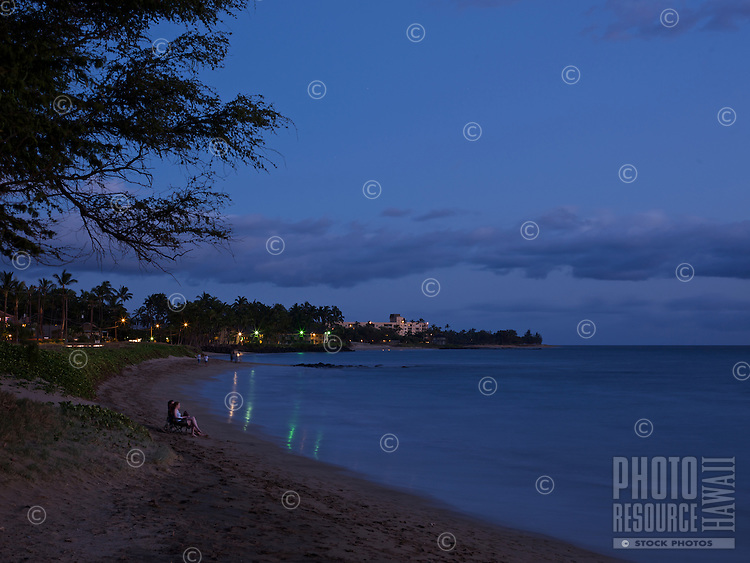 A couple sitting quietly on a calm beach at night in Kihei, Maui.