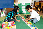 education preschool boy and girl working together putting together floor puzzle