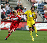 Columbus Crew defender Gino Padula (4) heads the ball while Chicago Fire midfielder Chris Rolfe (17) looks on.  The Columbus Crew tied the Chicago Fire 2-2 at Toyota Park in Bridgeview, IL on September 20, 2009.