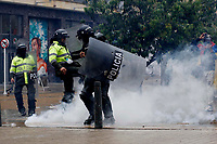 BOGOTA, COLOMBIA - MAY 05: A police officers kick a  gas canister during national strike on May 5, 2021 in Bogota, Colombia. Despite that the ruling party announced withdrawal of the unpopular bill for a tax reform and the resignation of the Minister of Finances, social unrest continues after a week. The United Nations human rights office (OHCHR) showed its concern and condemned the riot police repression. Ongoing protests take place in major cities since April 28. (Photo by Leonardo Munoz/VIEW press/Corbis via Getty Images)