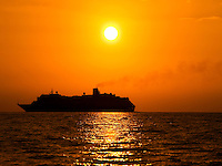 A cruise ship sails in the sunset near Hawai'i.
