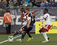 New England Revolution defender Chris Tierney (8) works to keep ball in play as New York Red Bulls midfielder Lloyd Sam (10) pressures. New England Revolution forward Dimitry Imbongo (92). In a Major League Soccer (MLS) match, the New England Revolution (blue) tied New York Red Bulls (white), 1-1, at Gillette Stadium on May 11, 2013.