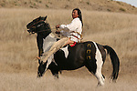 A Native American Indian riding bareback on his war marked painted horse in South Dakota