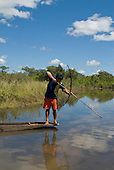 Xingu Indigenous Park, Mato Grosso State, Brazil. Aldeia Waura; a young warrior fishing from a dugout canoe with bow and arrow.