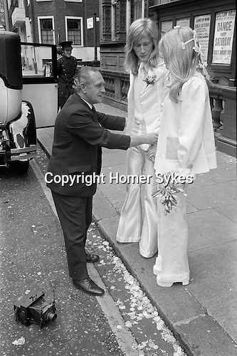 Caxton Hall Westminster London. Londons main register office until 1979. White wedding his and her uni sex clothes trouser suits flares or bell bottoms and cuban healed shoes. Long hair. 1970s fashionable London. ..<br /> He is Michael Stephens I think a well know hairdresser of the time. If you know otherwise please let me know.