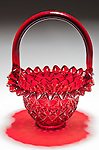 Looking into a red candy bowl,shaped like a basket with light from above, reflection and shadow on white gradiated background.