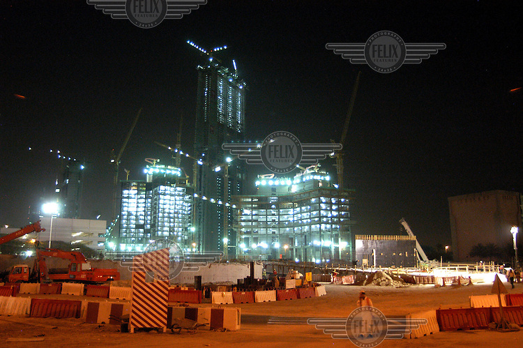 A building under construction is illuminated at night.