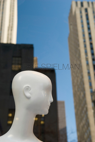AVAILABLE FROM JEFF AS A FINE ART PRINT.<br /> <br /> AVAILABLE FOR COMMERCIAL AND EDITORIAL LICENSING FROM GETTY IMAGES.  Please go to www.gettyimages.com and search for image # 139059560.<br /> <br /> Mannequin in Department Store Window on Fifth Avenue with Reflection of Rockefeller Center Buildings in the Background, Midtown Manhattan, New York City, New York State, USA