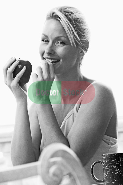 Portrait of young blonde woman with apple