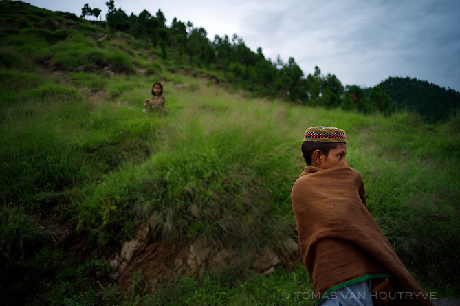 A Pashtun boy covers his face near the village of Barhampati in the Swat valley, Pakistan, on Aug. 25, 2010.