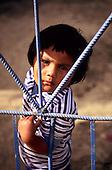 Putina Punco, Peru. A young girl behind a blue wrought iron gate.