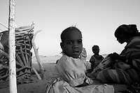 Tine, Tchad, June 9, 2004.Aziza, center, a Sudanese refugee awaits hypothetical transport to reach a new camp set up in Mile, more than 150km away.