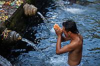 Bali, Indonesia.  Young Man Praying at Tirta Empul, a Spring Sacred to Balinese Hindus.
