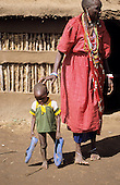 Lolgorian, Kenya. Siria Maasai Manyatta; woman and toddler, traditional beadwork earrings, blue plastic shoes.