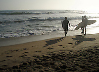 Surfers look for waves while walking along the beach.