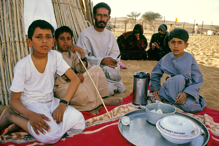 Wahiba Sands, Oman, Arabian Peninsula, Middle East - A bedouin family.  The father and two sons are wearing the traditional Arabian robe, a dishdasha.  The son on the left wears a t-shirt and the traditional wizar or lunghi, a  garment similar to a Far Eastern sarong, which is wrapped around the body from the waist, often worn under a dishdasha.  The second boy from the left holds a traditional walking stick, the asa or khuzran.  In lieu of a veil, women of the Wahiba sands often wear a birqa, or mask, as does the one on the left.
