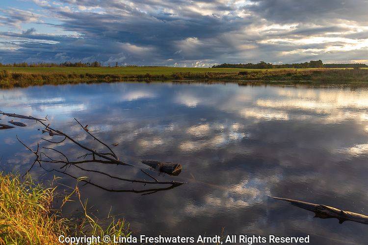 The morning clouds start to clear over a farmer's pond in northern Wisconsin.