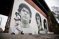 NEW YORK, UNITED STATES - NOVEMBER 25: A man walk pass in front of a mural of Diego Marado's face  under the Manhattan Bridge on November 25, 2020. Argentine soccer legend Diego Maradona died at the age of 60, his spokesman announced on November 25 2020. (Photo by Pablo Monsalve/VIEWpress via Getty Images)