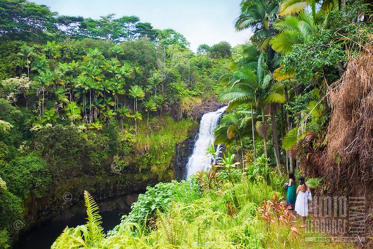 Female tourists visiting Kulaniapia Falls, tropical rainforest jungle, Hilo, Big Island.