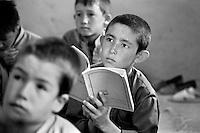An ethnic Hazara boy studies in an improvised classroom near Bamiyan, Afghanistan on June 29, 2002.