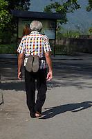 Borobudur, Java, Indonesia.  Man Walking Barefoot around the Temple, Performing Pradaksina, Circumambulating the Temple in a Clockwise Direction.