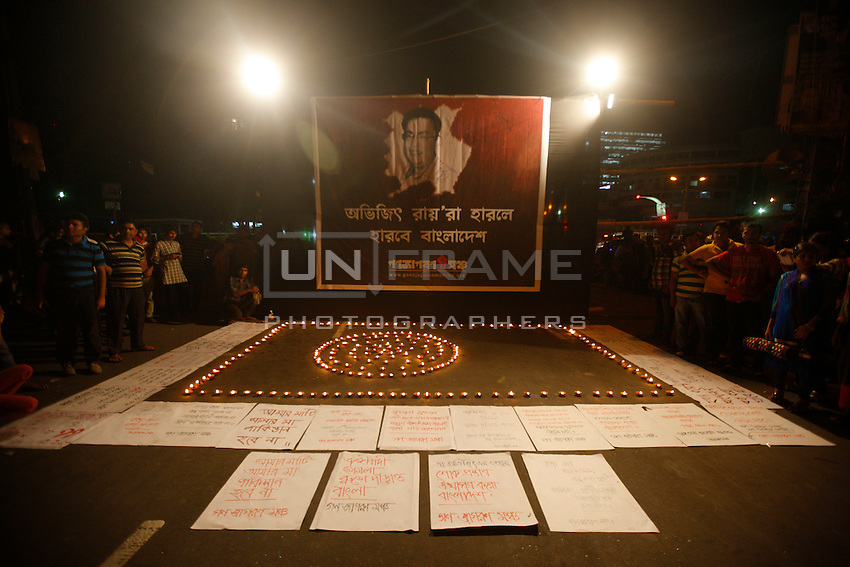 A Bangladeshi activist lit candles in front of a portrait of Avijit Roy as others gather during a protest against the Roy in Dhaka, Bangladesh. Friday, Feb. 27, 2015.