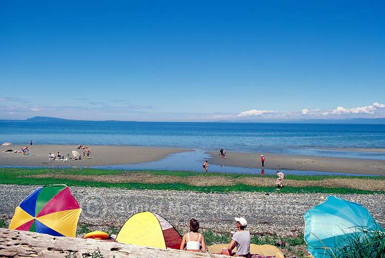 "People sunbathing on the Beach and wading in the Pacific Ocean at Qualicum Beach, in the ""Oceanside Region"" of Vancouver Island, British Columbia, Canada"