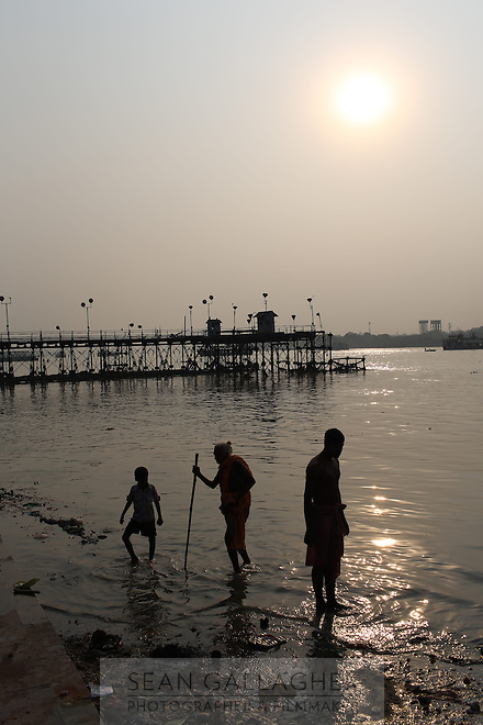 People wash in the Ganges River at sunset near the Howrah bridge in Kolkata. Upon entering the city, the river is saturated with a mix of domestic and industrial waste that has accumulated as it has passed through numerous states in northern India, making it one of the most polluted rivers in the world. India. November, 2013