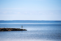 Boy fishing from a jetty, Cape Cod, Wellfleet, Massachusetts, USA