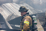 A firefighter digging through debris from a collapsed burnt building from a fire