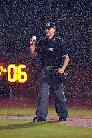 Umpire John Bostwick just before calling the game due to the rain, standing in front of the implemented pitch clocks, between the Mississippi Braves and Mobile BayBears on April 28, 2015 at Hank Aaron Stadium in Mobile, Alabama.  The game was suspended after the top of the second inning with Mobile leading 3-0, the BayBears went on to defeat the Braves 6-1 the following day.  (Mike Janes/Four Seam Images)