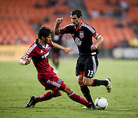 Chris Pontius (13) of D.C. United has the ball tackled away from him by Arne Friedrich (23) of the Chicago Fire at RFK Stadium in Washington, DC.  D.C. United defeated the Chicago Fire, 4-2.
