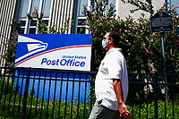 WEST NEW YORK, NJ - AUGUST 17: People pass walk by the United States Postal Service office on August 17, 2020 in West New York,  New Jersey. Mail Delays Fuel Concern Trump Is Undercutting Postal System before elections , Mail-in voting across the country has led to a series of anomalous results in recent weeks (Photo by Kena Betancur/ VIEWpress via Getty Images)