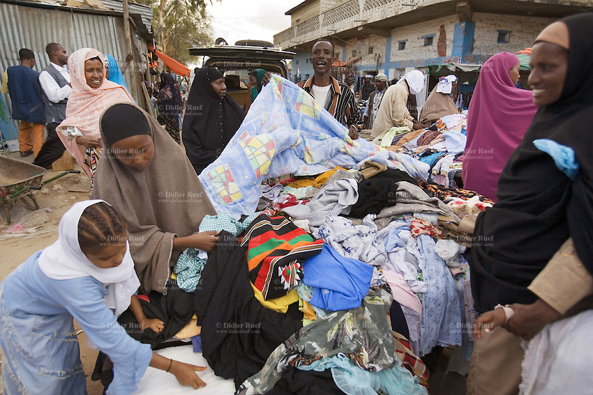 Somaliland. Waqohi Galbed province. Hargeisa. A black muslim man is selling clothes to black muslim women, wearing veils on their heads, on a market stall. Somaliland is an unrecognized de facto sovereign state located in the Horn of Africa. Hargeisa is the capital of Somaliland. © 2006 Didier Ruef