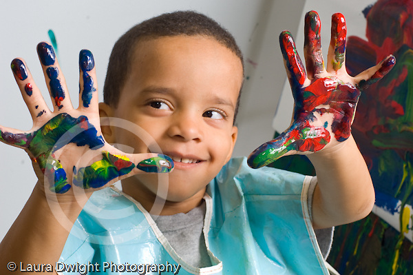 Education preschoool children ages 3-5 art activity proud boy in smock showing off his hands that he painted in many colors or pressed against his painting horizontal