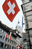 Switzerland. Zoug.  Swiss flag and zoug flag (blue and white) float in the old town. © 1989 Didier Ruef